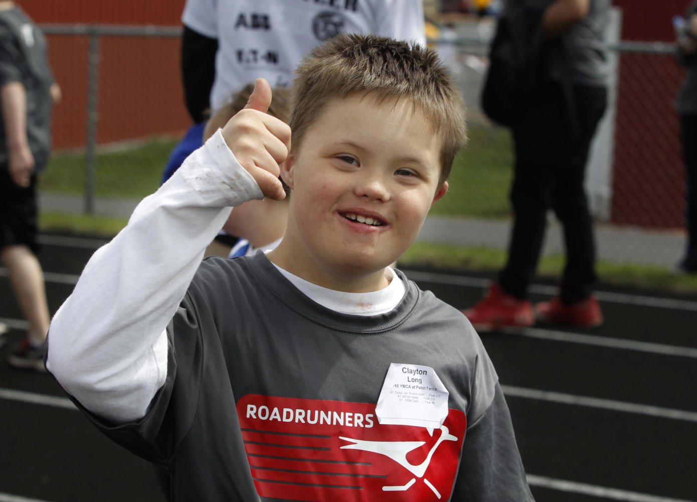 Clayton Long, representing the YMCA at Pabst Farms, is all smiles after he competes and crosses the line in the 100 meter dash. Over 1800 special olympic athletes from the the  greater-Milwaukee area competed in track and field events with  first-, second- and third-place finishers able to qualify for a place in the Special Olympics Wisconsin State Summer Games. The event took place at Muskego High School, Saturday, May 4, 2013.  Journal Sentinel photo by RICK WOOD/ RWOOD@JOURNALSENTINEL.COM